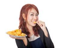 Glückliches asiatisches Mädchen essen einen Kartoffelchip Stockfotografie