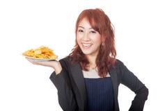 Glückliches asiatisches Mädchenlächeln mit einem Teller von Kartoffelchips Stockbild