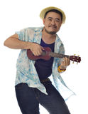 Glückliches asiatisches Manntanzen und Spielen des Ukuleleisolathintergrundes Lizenzfreies Stockfoto