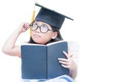Glückliches asiatisches Schulkindergraduiertes Denken mit Staffelungskappe Stockfotos