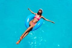 Glückliches attraktives Schwimmen der jungen Frau im Pool lizenzfreies stockbild