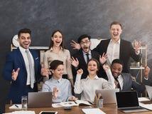 Glückliches aufgeregtes Geschäftsteam, das Laptop betrachtet stockbilder