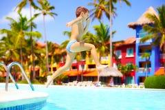 Glückliches aufgeregtes Kind, das in Pool auf Sommerferien springt Stockbilder