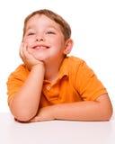 Glückliches aufmerksames Kind, das am Schreibtisch sitzt Stockfotos