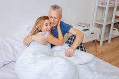 glückliches Aufwachen des Blond-haarigen Fraugefühls mit ihrem Ehemann stockbild