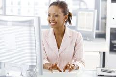 Glückliches Büroangestelltmädchen am Schreibtisch Stockbild