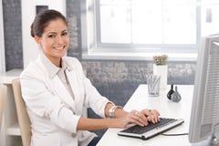 Glückliches Büromädchen, das an Computer arbeitet Stockbild