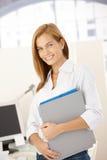 Glückliches Büromädchen mit Faltblättern Stockfotos