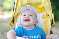 Glückliches Baby auf gelbem Kinderwagen im Sommer Stockbild