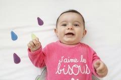 Glückliches Baby, das auf seiner Bettkrippe liegt Lizenzfreies Stockfoto