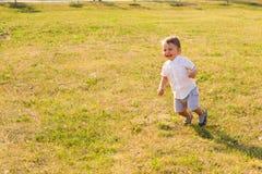 Glückliches Baby, das auf Sommerfeld läuft lizenzfreie stockfotos