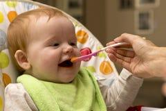 Glückliches Baby, das Brei isst Stockbild