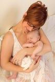Glückliches Baby, das in den Armen der Mutter schläft Stockfotografie