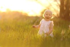 Glückliches Baby, das in der Natur bei Sonnenuntergang spielt Lizenzfreie Stockfotos
