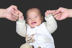 Glückliches Baby, das Elternfinger im schwarzen Hintergrund hält Stockfoto
