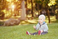 Glückliches Baby, das im grünen Gras sitzt Lizenzfreie Stockfotos