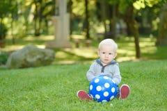 Glückliches Baby, das im grünen Gras sitzt Stockfotos