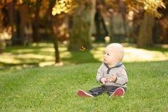 Glückliches Baby, das im grünen Gras sitzt Lizenzfreies Stockbild