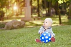 Glückliches Baby, das im grünen Gras sitzt Lizenzfreie Stockbilder