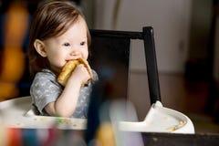 Glückliches Baby, das im Hochstuhl isst Stockfoto