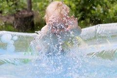 Glückliches Baby, das im Pool auf dem Hinterhof spielt Wässern Sie Spritzen Reisenkoffer mit Meerblick nach innen Lizenzfreie Stockfotografie