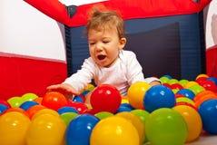 Glückliches Baby, das mit Bällen spielt Lizenzfreies Stockfoto
