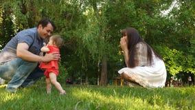 Glückliches Baby, das mit Eltern im Park spielt Fröhliche Mutter und Vati gehen mit ihrer Tochter im Park Familienwerte stock footage