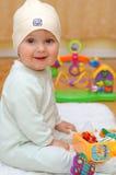 Glückliches Baby, das mit seinen Spielwaren sitzt Lizenzfreie Stockfotos