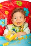 Glückliches Baby, das Püree isst Stockfotografie