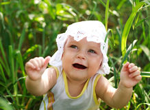 Glückliches Baby, das Spaß im grünen Gras hat Stockfotos