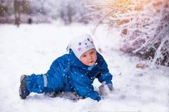 Glückliches Baby, das Spaß im Winterpark hat Stockfoto