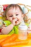 Glückliches Baby, das von der Flasche trinkt Lizenzfreie Stockfotos