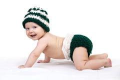 Glückliches Baby in der Strickmütze, die über Weiß kriecht Stockfotos