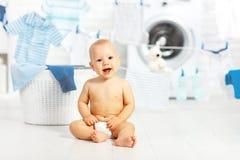 Glückliches Baby des Spaßes, zum von Kleidung und von Lachen in der Wäscherei zu waschen Stockbild