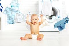 Glückliches Baby des Spaßes, zum von Kleidung und von Lachen in der Wäscherei zu waschen Stockfoto