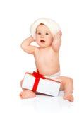 Glückliches Baby in einem Weihnachtshut mit einem Geschenk lokalisiert Lizenzfreie Stockfotos