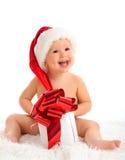 Glückliches Baby in einem Weihnachtshut mit einem Geschenk lokalisiert Lizenzfreie Stockfotografie