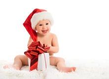 Glückliches Baby in einem Weihnachtshut mit einem Geschenk lokalisiert Lizenzfreie Stockbilder