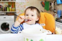 Glückliches Baby isst zu Abend Stockfotografie