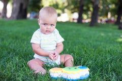 Glückliches Baby mit dem hellen und flaumigen Haar, das auf dem Gras und dem Lachen sitzt Lizenzfreie Stockfotografie