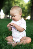 Glückliches Baby mit dem hellen und flaumigen Haar, das auf dem Gras sitzt Lizenzfreie Stockfotos