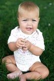 Glückliches Baby mit dem hellen und flaumigen Haar, das auf dem Gras sitzt Stockbild