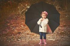 Glückliches Baby mit einem Regenschirm im Regen, der auf Natur spielt Lizenzfreie Stockfotos