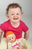 Glückliches Baby mit ihrer Puppe auf grauem Hintergrund stockbild