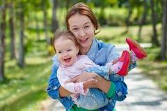 Glückliches Baby in seinem mother& x27; s-Hände Stockfotos
