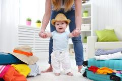 Glückliches Baby taddler macht den ersten Schritt mit Mutter und Taschen zu lizenzfreies stockfoto