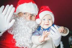 Glückliches Baby und Santa Claus sagen Guten Tag und bewegen Hand wellenartig Lizenzfreie Stockbilder