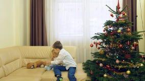 Glückliches Baby und sein Spiel des größeren Bruders mit Teddybärabschluß verzierten Weihnachten, lächelndes Bruderspiel nahe Win stock video footage