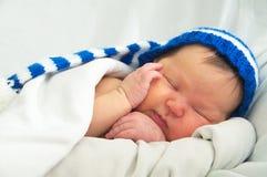 Glückliches Babygesicht im Hut, neugeboren mit Gelbsucht auf weißer Decke, Säuglingsgesundheitswesen lizenzfreies stockfoto