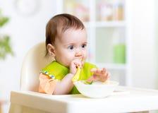 Glückliches Babykind, das im Stuhl mit einem Löffel sitzt lizenzfreie stockbilder